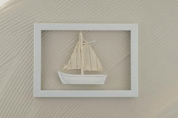 Summer sea frame.white boat in a white frame on the sand background.Summer season. Vacation.Summer time.Sea style.interior summer frame