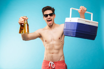 Portrait if a cheerful shirtless man in swimming shorts