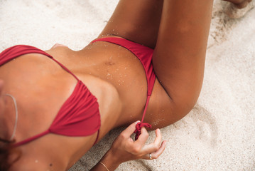 Close-up tanned parts of female body on the beach with white sand. Sexy model in a red bikini. Woman in a swimsuit on summer vacation.