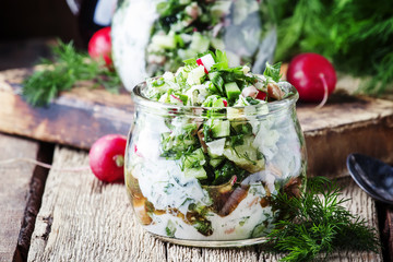 Okroshka - Traditional Russian cold summer soup with vegetables, meat and herbs, dressed with bread kvass and kefir, old wooden background, selective focus