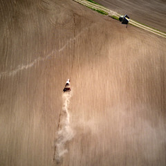 Wall Mural - Aerial view tractor with a cultivator for seeds at the beginning of the spring season of agricultural work