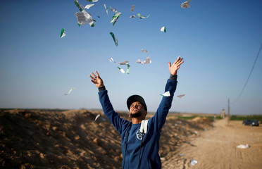 Palestinian man throws leaflets dropped by the Israeli military during a protest against U.S. embassy move to Jerusalem and ahead of the 70th anniversary of Nakba, at the Israel-Gaza border, east of Gaza City