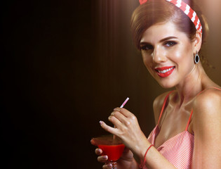 Pin up girl drink bloody Mary cocktail. Pin-up retro female style. Girl wearing red dress seduces men. Plan budget for party. Brown sepia photo with sun flare warm-glow and lens flare .