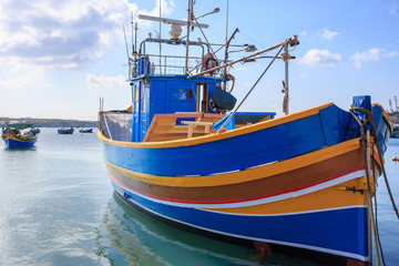 Traditional fishing boat, luzzu, anchored at Marsaxlokk, Malta. Blue sky with clouds and village background. Close up view.