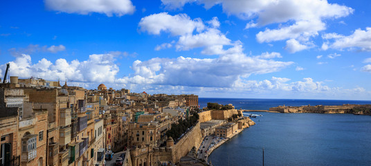 Malta, Valletta. Grand harbor in mediterranean. Blue sea and blue sky with few clouds background. Panoramic view, banner.