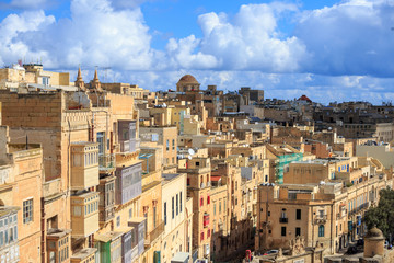 Malta, Valletta. Capital with tall traditional limestone buildings, under a blue sky with few clouds.