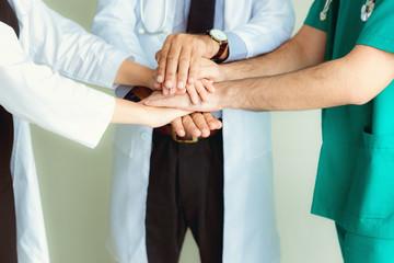 Close up portrait of doctors teamwork stacking hands together at hospital