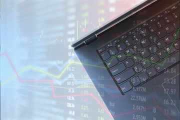 Laptop for finance use and stock trading with market charts overlay.  Confusion and trade strategy unpredictable.
