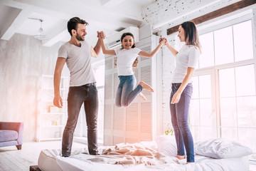 The beautiful family jumping on the bed