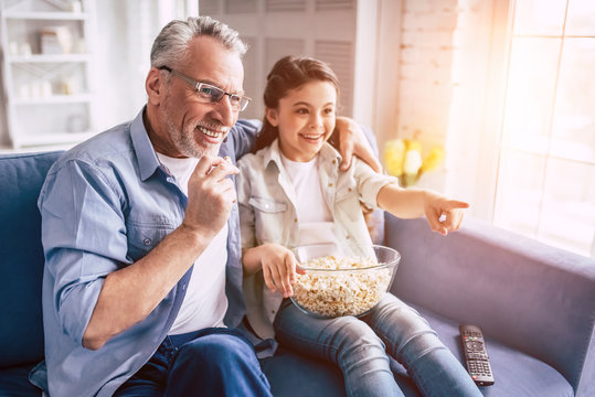 The little girl and a grandfather wathing tv with a popñorn