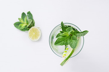 Cold spring drink with cucumber, pieces of lime, fresh leaves mint and ice cubes on soft white background, top view, closeup.