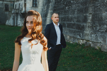 Wedding couple is walking outdoors in sunny green summer day. Medieval stone walls with old renaissance palace on background. Groom is looking at bride is satin lace dress. Old castle architecture.