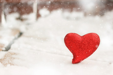 Red glitter heart in the winter snow