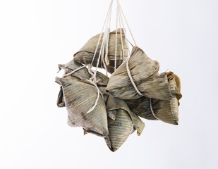 A bunch of zongzi or rice dumpling with a hand hold on them on Dragon Boat Festival, Asian traditional food, white background