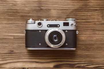 Old film photo camera isolated on brown wooden background.