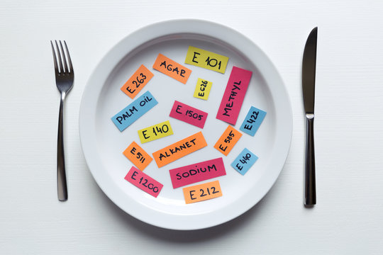 Colorful paper notes naming food additives on plate with fork and knife, food additive and unhealthy food concept.
