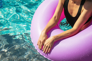 womans arm on the pink swim ring in the swimming pool. Summer Vacation. Enjoying suntan. Weekend on luxury resort