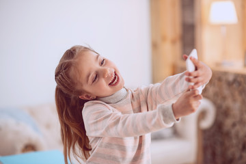 My photo. Delighted happy girl looking at the smartphone camera while taking selfie