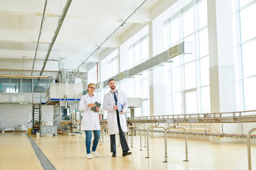 Two highly professional technologists wearing white coats walking along production department of modern milk factory and discussing work-related issues