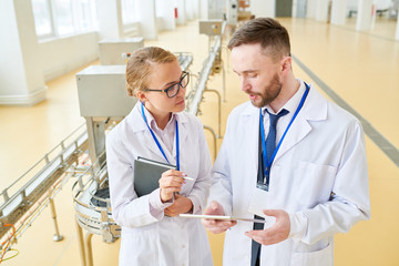 Handsome bearded technologist wearing white coat showing statistic data concerning production quantity to female colleague with help of digital tablet while standing at spacious dairy factory.