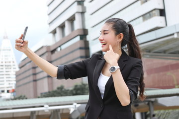Cheerful young Asian woman taking a picture or selfie with mobile smart phone outdoors