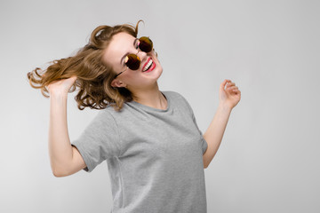 Charming young girl in a gray T-shirt on a gray background. Cheerful girl in round glasses holds a hand of hair