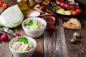 Bowls of fresh vegetable salad with cabbage and radish
