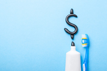 Black toothpaste from charcoal for white teeth. Tooth-paste in the form of  dollar sign,  tube and  dental counter on  blue background. The concept of expensive toothpaste? Copy space for text