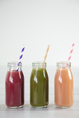 Three Different Fruit Smoothy on a White Wood Table - Berry, Green, and Strawberry Banana