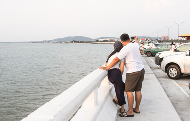 Couple taking self portrait photos with smartphone on bridge at Ang Sila Chonburi Thailand, Selfie photography