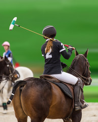 Polo woman player is riding on a horse.
