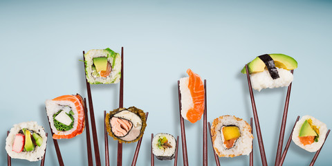 Traditional japanese sushi pieces placed between chopsticks, separated on light blue pastel background.
