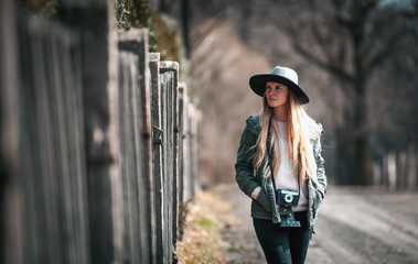 Woman with vintage camera and hat walking on rural country