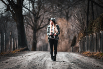 Woman with vintage camera and hat walking on road at rural country