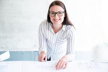 Frau mit Plänen auf einer Baustelle