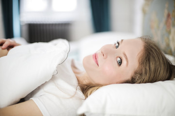 Smiling girl lying in bed