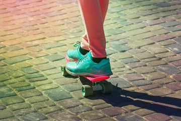 young skateboarder legs in pink tights and blue sneakers skateboarding at skate park