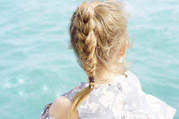 preteen girl sitting on a pier by the sea