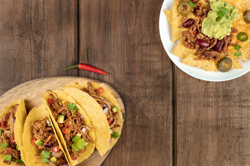 Mexican food with copy space, overhead photo of hot spicy tacos and nachos