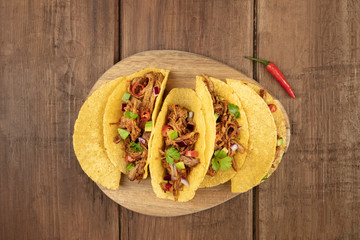 Overhead photo of Mexican tacos with pulled meat, avocado, chili peppers, cilantro, with place for text