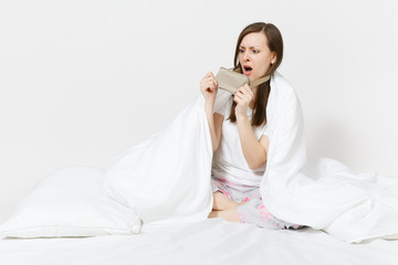 Fun tired young woman sitting in bed with sleep mask, sheet, pillow, wrapping in blanket isolated on white background. Beauty female spending time in room. Rest, relax, good mood concept. Copy space.
