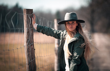 Beautiful stylish woman in hat on rural country farm