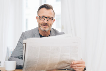 Mature man wearing glasses reading newspaper