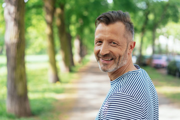 Cheerful mature man standing in park