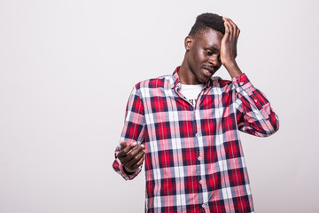 Upset and sad african man grabbing his forehead with hand standing missing the diversity lottery application deadline or forgetting to turn of electricity at home over white background.