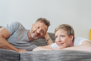 Mature woman with man relaxing on sofa at home