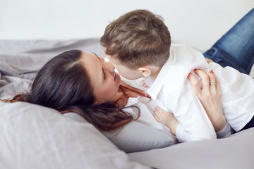 Mom hugging her son and a bed at home. Maternity concept. Parenthood. Motherhood