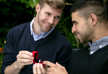 Engagement proposal betwen two gay men as one man proposes with an engagement ring in red box