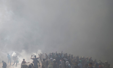 Palestinian demonstrators gather at the Israel-Gaza border as smoke rises during a protest against U.S. embassy move to Jerusalem and ahead of the 70th anniversary of Nakba, east of Gaza City