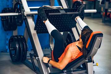 Young sporty woman does leg exercises in gym